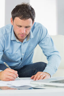 Content casual man writing on sheets paying bills in bright living room